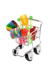 Party novelties in mini shopping cart on white background