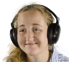 Young woman listening to music on headphones. Isolated on white