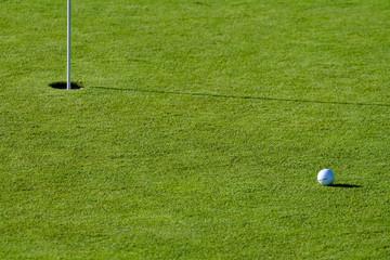 golf ball near the hole on a putting field