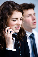 Young businesswoman talking on landline phone at office.