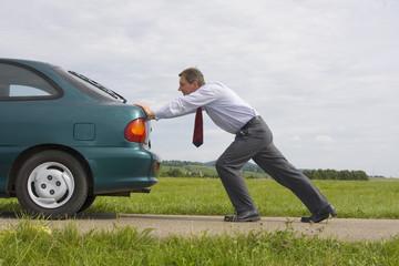 Geschäftsmann schiebt grünes Auto