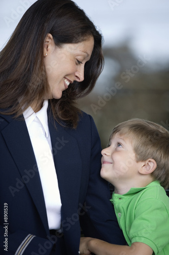 View of a cute boy and his mother in uniform smiling.