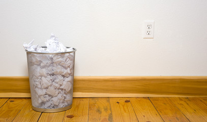 a wire mesh office trash can with crumpled paper