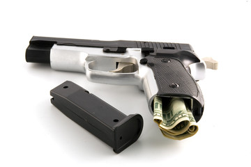 The pistol loaded by dollars . Isolated object.