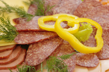 Slices of salami decorated with pepper rings, close-up