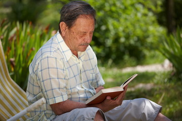 Healthy looking senior man is his late 70s reading in garden