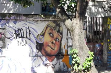 Petite fille tirant la langue derrière un arbre. Brésil.