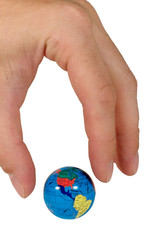 Human fingers ready to seize a small globe (isolated on white)