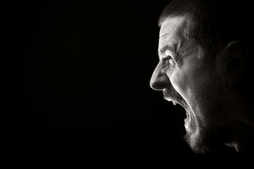 Face of screaming angry man on black background