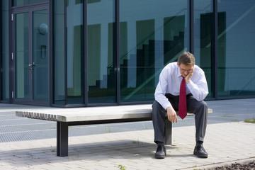 Müder Geschäftsmann sitzt auf Bank vor Bürogebäude