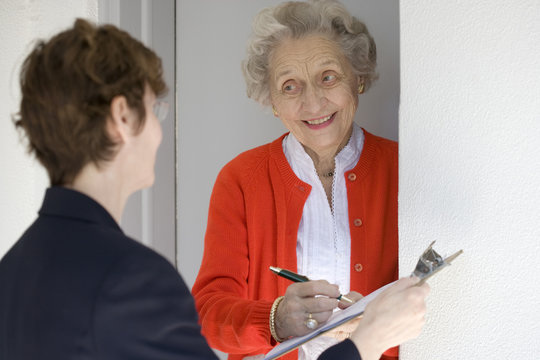 Attractive senior woman signing a document at front door