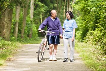 A couple senior asian talking and exercising at a park