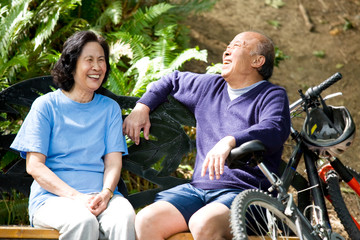 A shot of senior asian couple sitting on a bench at a park