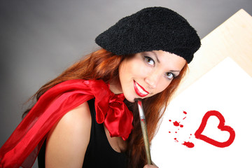 beautiful artist is painting red heart