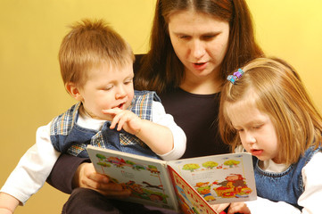 Mother withher children reading a pictures book