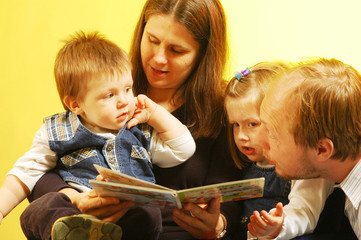 Father and mother with their children reading a pictures book
