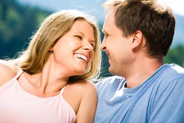 Joyful woman laughing while looking at smiling man