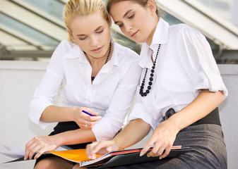 picture of two businesswomen working with documents