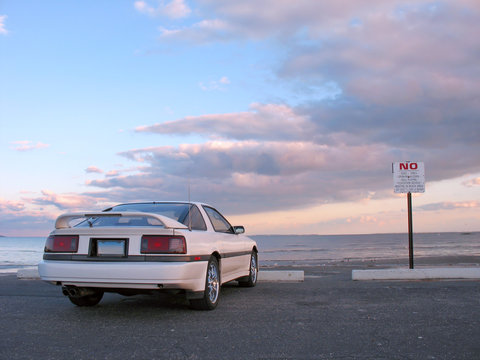 A customized white sports car parked at the beach.