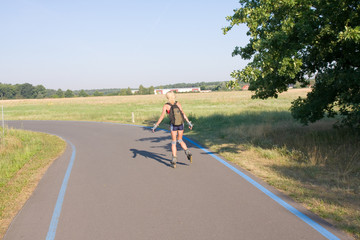 young female rollerskating on paved road