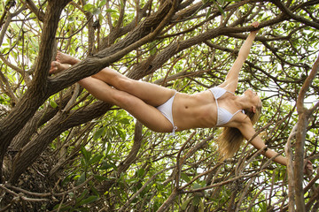 Woman hanging from tree.