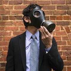 Businessman wearing gas mask.