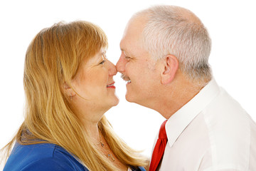 Adorable mature couple in love rubbing noses. Isolated