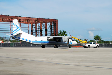 Pickup truck towing a turboprop cargo airplane