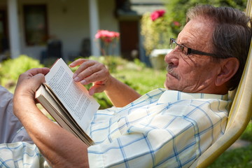 Healthy looking senior man is his late 70s reading book
