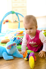 Baby girl (9 months) playing with soft toys at home.