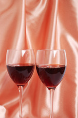 Two glasses with red wine on a beige satin background