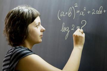 Teacher writing math formulas on blackboard