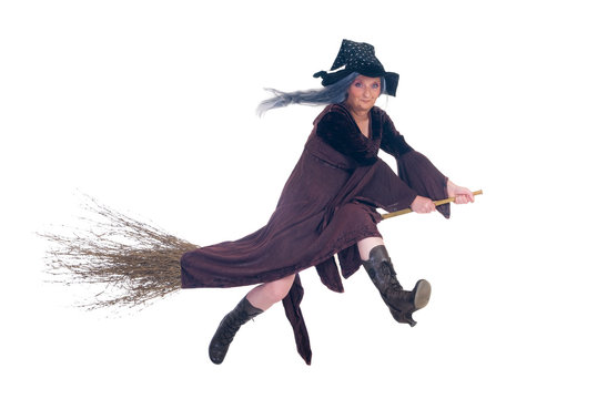 Middle aged Halloween witch flying on broom.