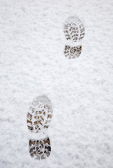 Two footprints in the snow on a wooden deck.
