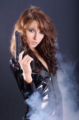 Sexy woman  holding gun . smoke background