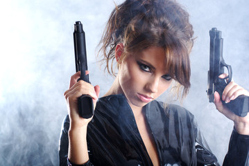 Sexy woman  holding gun . smoke background
