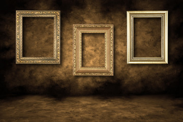 Three Guilded Picture Frames Hanging on a Grungy Wall