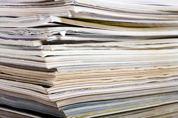 Stack of newspaper on neutral background close up