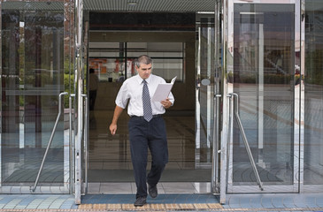 Businessman getting out of a corporate buidling