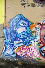 Tagueur bleu sur mur peint.