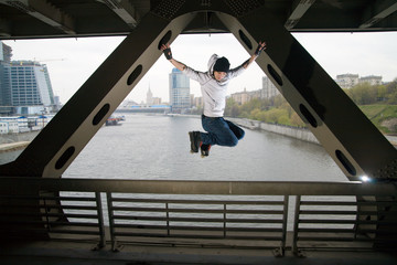 Roller man jumping at bridge over Moscow river.