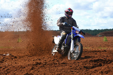 Off-road motorbike in extreme dirt. A lot of flying dirt.