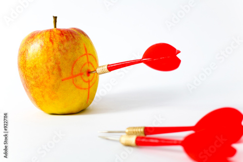 Red Yellow Apple With Darts On White Background Stock Photo And