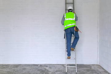 Workman in reflective vest and hard hat climbing a ladder