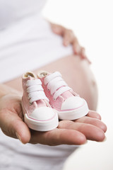 Pregnant woman holding pair of pink shoes for baby girl