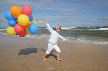 Cute girl with colour balloons on the beach