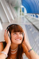 Smiling girl listening to music in big headphones