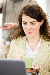 Young happy businesswoman working on laptop at office