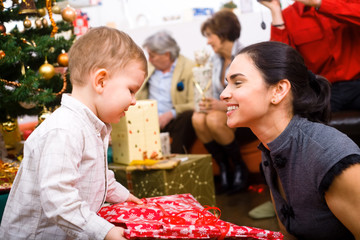 Little boy ( 3 years ) and mother giving Christmas present