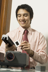 Man smiling as he looks at a slide next to a projector. Vertical
